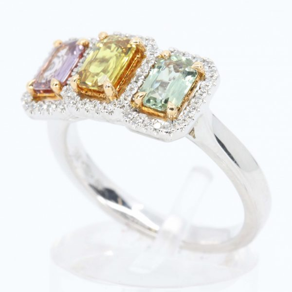Multi-coloured Sapphire Trilogy Ring with Halo of Diamonds Set in 18ct White Gold with Rose Gold Claws