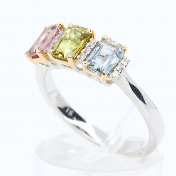 Multi-coloured Sapphire Trilogy Ring Separated by Diamond Accents Set in 18ct White Gold