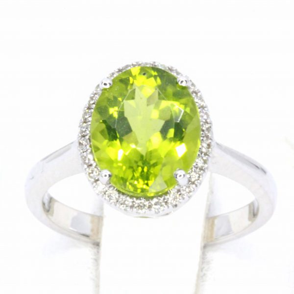Oval Shape Peridot Ring with Halo of Diamonds Set in 18ct White Gold