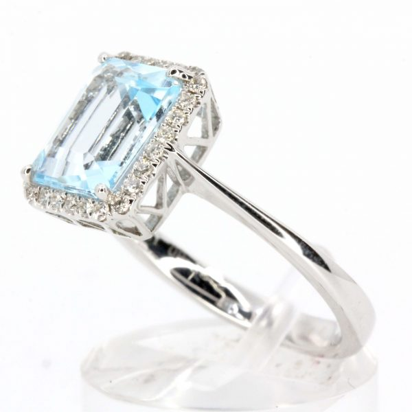 Emerald Cut Blue Topaz Ring with Halo of Diamonds Set in 18ct White Gold