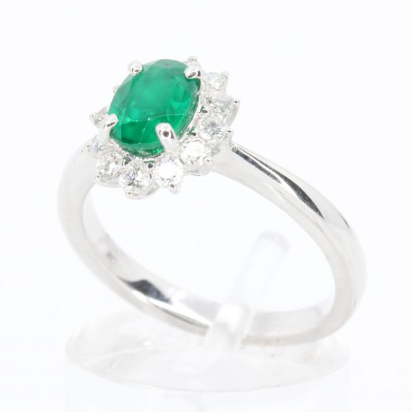 Oval Shape Emerald Ring with Halo of Diamonds Set in 18ct White Gold