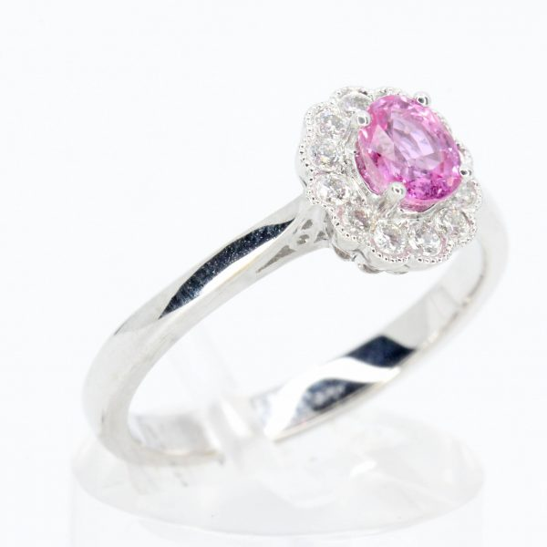 Oval Cut Pink Sapphire Ring with Halo of Diamonds Set in 18ct White Gold